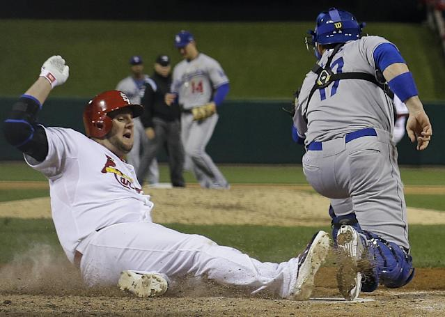 St. Louis Cardinals' Matt Adams slides safely past Los Angeles Dodgers catcher A.J. Ellis during the fifth inning of Game 6 of the National League baseball championship series, Friday, Oct. 18, 2013, in St. Louis. (AP Photo/David J. Phillip)