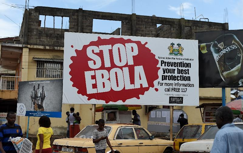 People walking past a billboard with a message about Ebola in Freetown, Sierra Leone