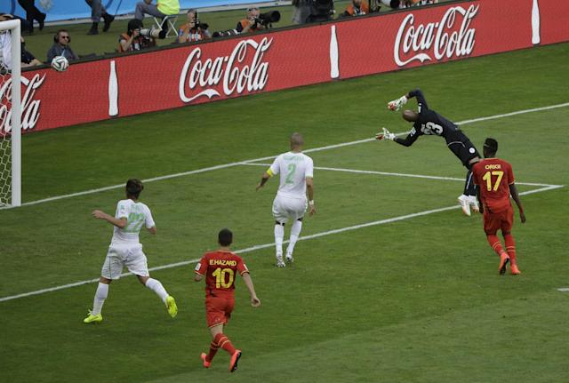The ball kicked by Belgium's Dries Mertens goes into the net past Algeria goalkeeper Cedric Si Mohamed during the group H World Cup soccer match between Belgium and Algeria at the Mineirao Stadium in Belo Horizonte, Brazil, Tuesday, June 17, 2014. From left Algeria's Mehdi Mostefa, Belgium's Eden Hazard and Belgium's Divock Origi. (AP Photo/Sergei Grits)