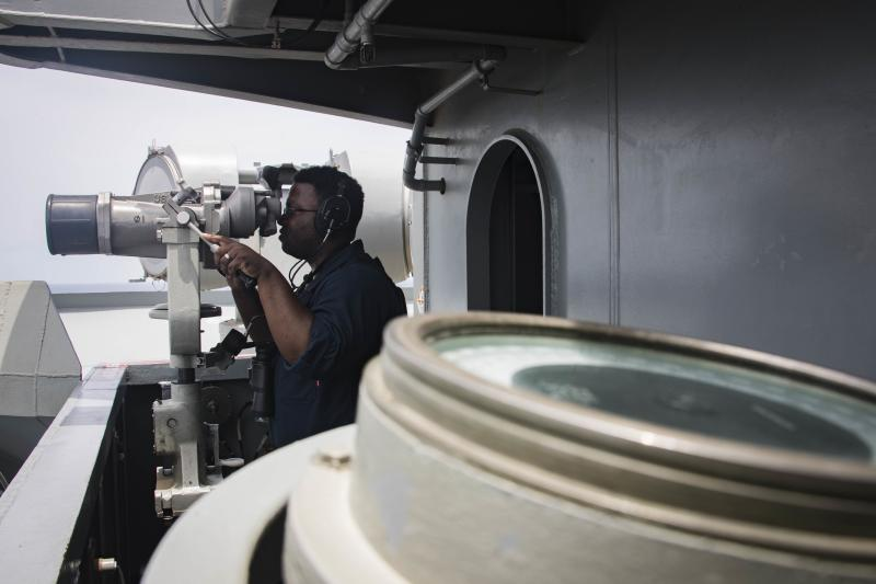 In this Sunday, May 19, 2019, photo released by the U.S. Navy, Boatswain's Mate Seaman Tabari Harvey, from Bellevue, Neb., stands watch as forward lookout on vulture's row aboard the Nimitz-class aircraft carrier USS Abraham Lincoln in the Arabian Sea. (Mass Communication Specialist 3rd Class Garrett LaBarge/U.S. Navy via AP)