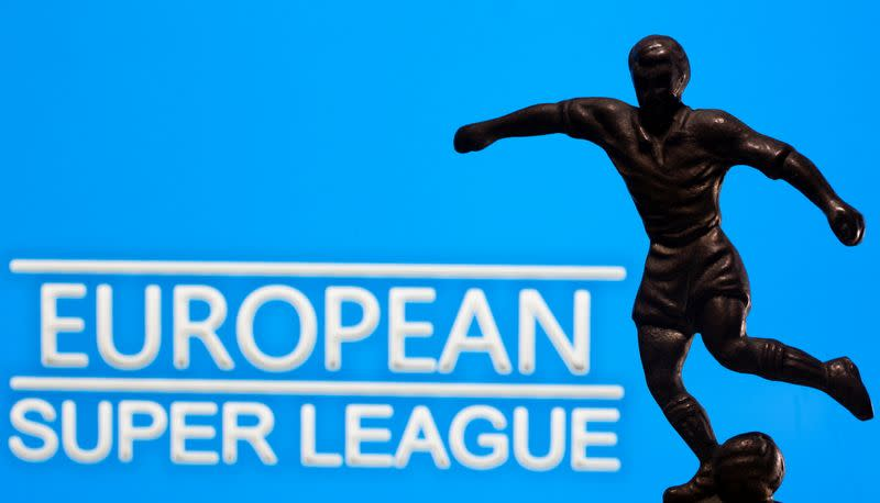 "A metal figure of a football player with a ball is seen in front of the words ""European Super League"" in this illustration"