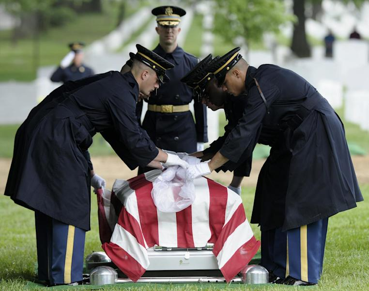 The protective covering is removed from the casket of Army Spc. 5 John L. Burgess, of Sutton Bay, Mich., who was the crew chief of a UH-1H Iroquois helicopter that crashed in 1970 in Binh Phuoc Province, South Vietnam, Tuesday, July 2, 2013, during the funeral services at Arlington National Cemetery in Arlington, Va. Burgess is buried with those who were also killed in the crash, 1st Lt. Leslie F. Douglas Jr., of Verona, Miss.; lst Lt. Richard Dyer, of Central Falls, R.I.; and Sgt. 1st Class Juan Colon-Diaz, of Comerio, Puerto Rico. The Pentagon says remains representing Burgess, Dyer and Colon-Diaz will be buried as a group in a single casket. (AP Photo/Susan Walsh)