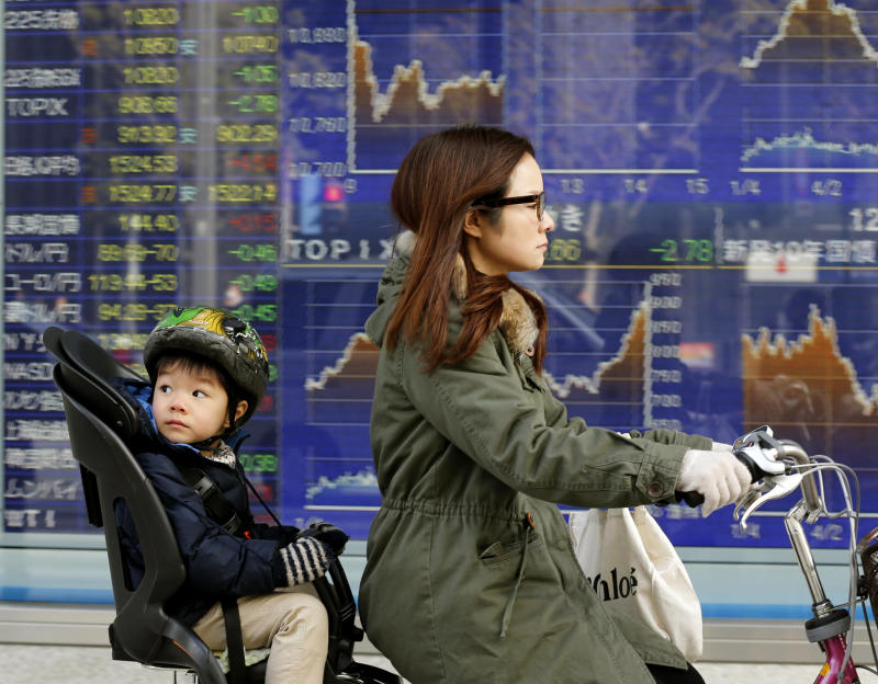 A mother and child cycle past an electronic stock board of a securities firm in Tokyo, Monday, Jan. 21, 2013. Asian stock markets were mixed Monday amid uncertainty about the outcome of a central bank meeting in Japan and nervousness over whether U.S. political leaders will be able to reach a deal on the government's debt limit.  (AP Photo/Koji Sasahara)