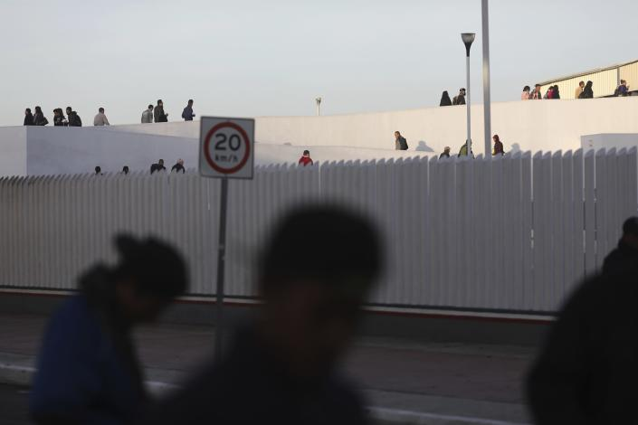Pedestrians cross the Chaparral border to the U.S. as migrants, foreground, begin to gather nearby, in Tijuana, Mexico, Friday, Nov. 23, 2018. The mayor of Tijuana has declared a humanitarian crisis in his border city and says that he has asked the United Nations for aid to deal with the approximately 5,000 Central American migrants who have arrived in the city. (AP Photo/Rodrigo Abd)