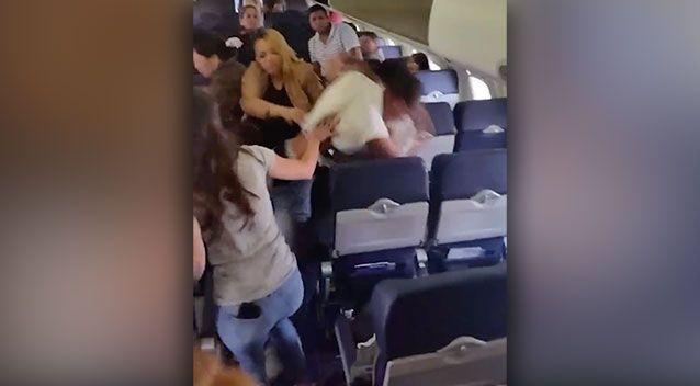Passengers try to break up the two men. Photo: Supplied