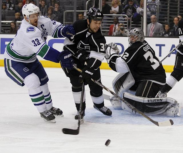 Vancouver Canucks center Henrik Sedin (33), of Sweden, and Los Angeles Kings defenseman Willie Mitchell (33) battle for the puck in front of goalie Jonathan Quick, right, during the first period of an NHL hockey game on Saturday, Jan. 4, 2014, in Los Angeles. (AP Photo/Alex Gallardo)