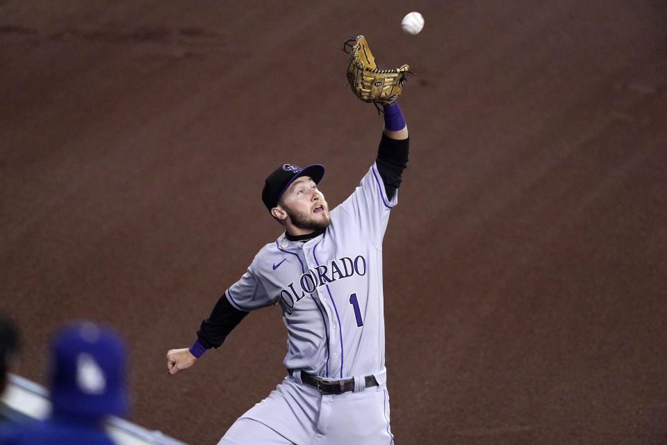 Colorado Rockies center fielder Garrett Hampson makes a catch at the wall on a ball hit by Los Angeles Dodgers' AJ Pollock during the second inning of a baseball game Tuesday, April 13, 2021, in Los Angeles. (AP Photo/Mark J. Terrill)