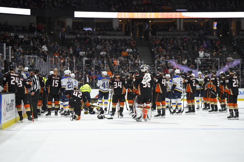 Members of the St. Louis Blues and Anaheim Ducks gather on the ice as Blues defenseman Jay Bouwmeester, who suffered a medical emergency, is worked on by medical personnel during the first period of an NHL hockey game Tuesday, Feb. 11, 2020, in Anaheim, Calif. (AP Photo/Mark J. Terrill)