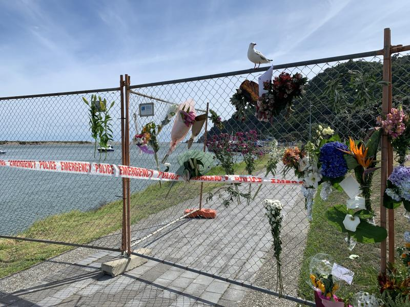 Tributes are seen on a fence near the water in Whakatane, New Zealand, Wednesday, December 11, 2019.