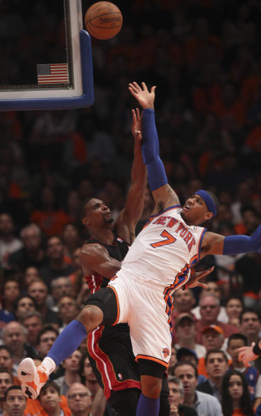 New York Knicks' Carmelo Anthony, right, tries to make a shot past Miami Heat's Chris Bosh, left, and is fouled by LeBron James in the first half of the NBA basketball game in New York, Sunday, April 15, 2012. (AP Photo/Seth Wenig)