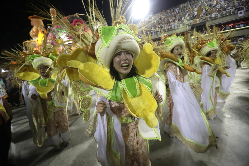 """Japanese performers from the Mangueira samba school, parade during carnival celebrations at the Sambadrome in Rio de Janeiro, Brazil, Tuesday, Feb. 12, 2013. While non-Brazilians have long shelled out hundreds of dollars for the right to dress up in over-the-top costumes and boogie in Rio's samba school parades, which wrapped up Monday in an all-night extravaganza, few in the so-called """"alas dos gringos,"""" or """"foreigners' wings,"""" know how to dance the samba well, bopping along goofily in the parades and waving at the crowds of spectators. (AP Photo/Silvia Izquierdo)"""