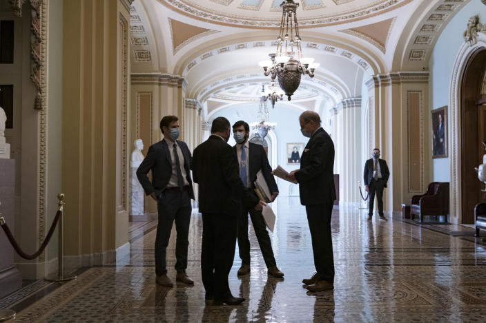 Congressional staffers wait in the ornate corridor outside the Senate chamber during a delay in work on the Democrats' $1.9 trillion COVID-19 relief bill, at the Capitol in Washington, Friday, March 5, 2021. (AP Photo/J. Scott Applewhite)