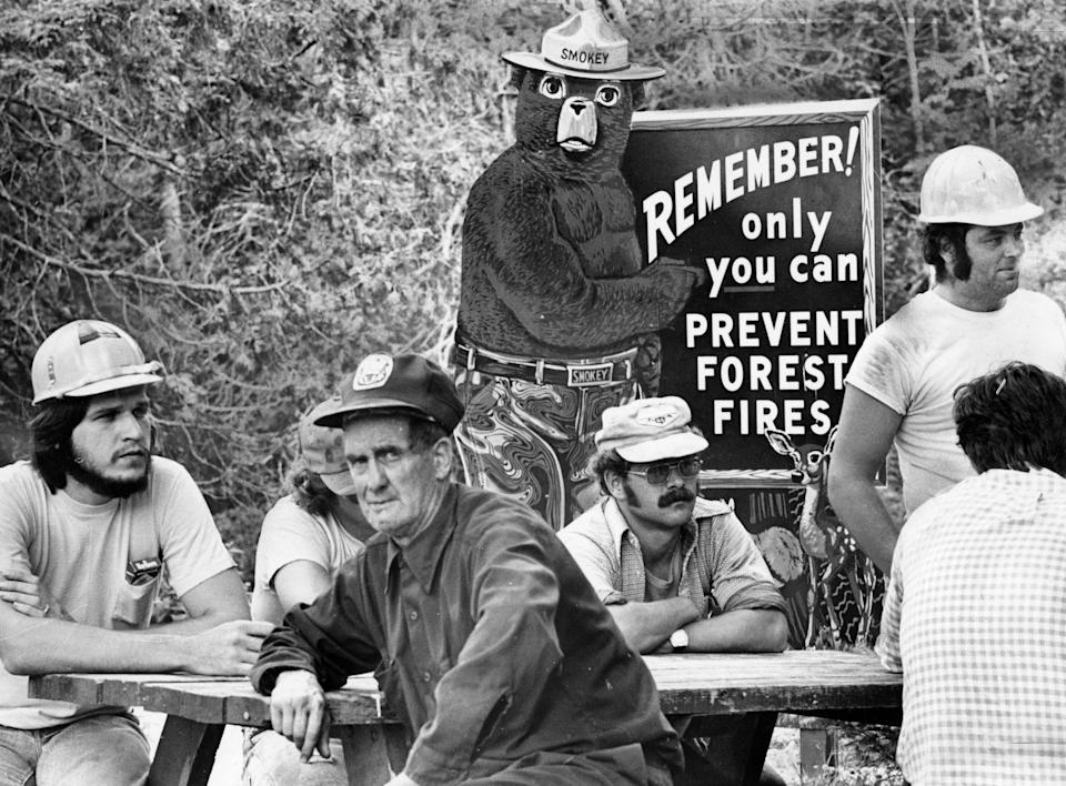 Smokey the Bear, the symbol of the nation's fire prevention efforts, stands watch at Togue Pond headquarters behind new crew awaiting transportation to fire lines of a forest fire in Millnocket, Maine, in 1977. (Photo: William Ryerson/The Boston Globe via Getty Images)
