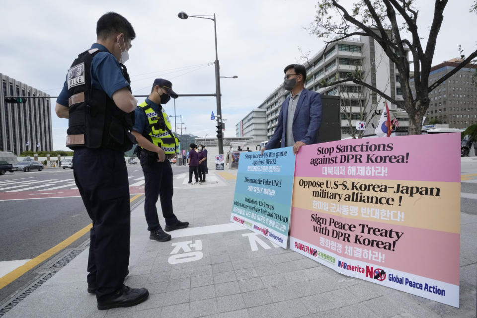 """A protester stands in protest to denounce the U.S. policies on North Korea as police officers watch near the U.S. Embassy in Seoul, South Korea, Tuesday, Sept. 28, 2021. North Korea on Monday accused the United States of keeping up its """"hostile policy"""" and demanded the Biden administration permanently end joint military exercises with South Korea even as it continued its recent streak of weapons tests apparently aimed at pressuring Washington and Seoul over slow nuclear diplomacy. (AP Photo/Ahn Young-joon)"""