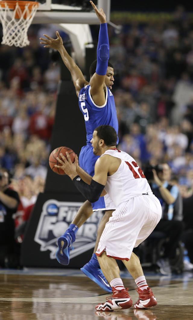 Wisconsin guard Traevon Jackson is fouled by Kentucky guard Andrew Harrison, top, while shooting a three-point basket near the end of an NCAA Final Four tournament college basketball semifinal game Saturday, April 5, 2014, in Arlington, Texas. Kentucky won 74-73. (AP Photo/Charlie Neibergall)