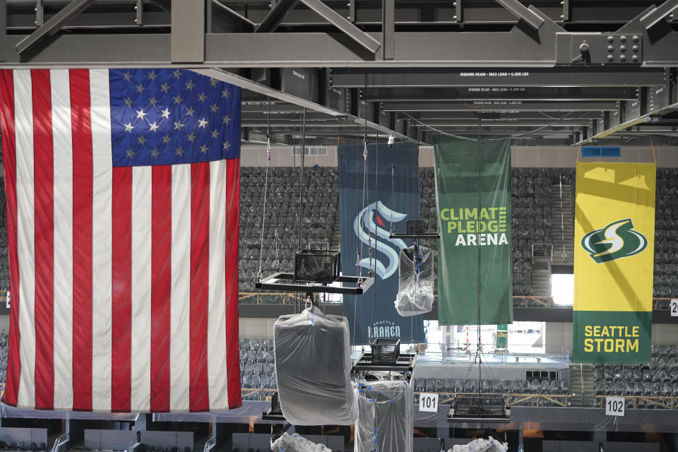 United States and team flags hang in the rafters of the Climate Pledge Arena during a media tour of the facility, Monday, July 12, 2021, in Seattle. The arena will be the home of the NHL hockey team Seattle Kraken and the WNBA Seattle Storm basketball team as well as hosting concerts and other performing arts events. (AP Photo/Ted S. Warren)