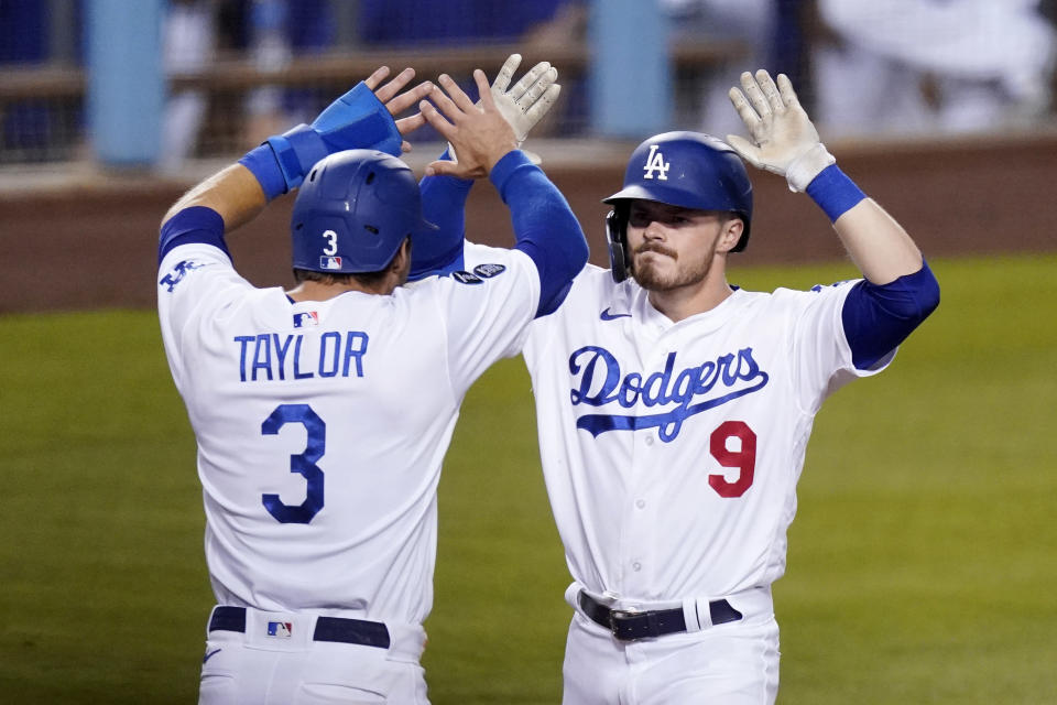 Los Angeles Dodgers' Gavin Lux, right, is congratulated by Chris Taylor after hitting a three-run home run during the eighth inning of an interleague baseball game against the Seattle Mariners Tuesday, May 11, 2021, in Los Angeles. (AP Photo/Mark J. Terrill)