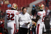 FILE - San Francisco 49ers assistant Katie Sowers talks with free safety D.J. Reed (32) and wide receiver Richie James (13) before an NFL football game against the Carolina Panthers in Santa Clara, Calif., in this Sunday, Oct. 27, 2019, file photo. (AP Photo/Tony Avelar, File)