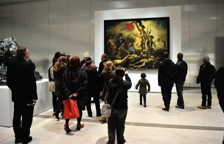 "People stand in front of Eugene Delacroix's masterpiece ""Liberty Leading the People"" on display in Lens, northern France, on December 4, 2012. One of the most iconic paintings in French history, Delacroix's ""Liberty Leading the People"", has been defaced by a woman allegedly suffering psychiatric problems, but no permanent damage was done"