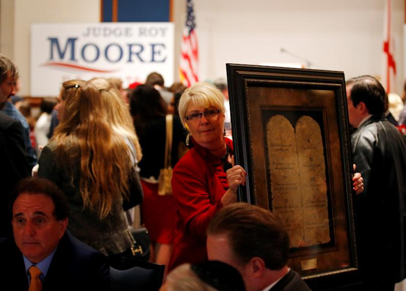 A framed Ten Commandments is being carried by a supporter at Republican Roy Moore's election party in Montgomery, Alabama, U.S., December 12, 2017. (Jonathan Bachman / Reuters)