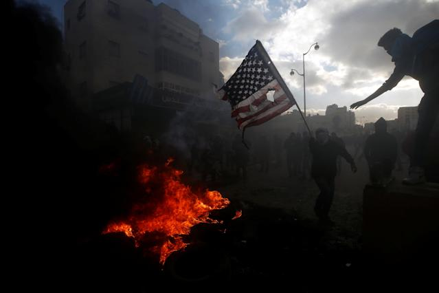 <p>A Palestinian protester prepares to burn a U.S. flag during clashes with Israeli troops at a protest against President Donald Trump's decision to recognize Jerusalem as the capital of Israel, near the Jewish settlement of Beit El, near the West Bank city of Ramallah, Dec. 7, 2017. (Photo: Mohamad Torokman/Reuters) </p>