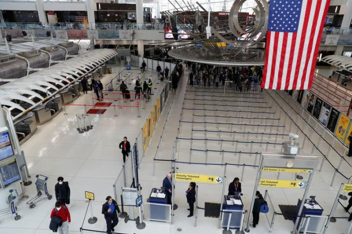 Passengers walk through Terminal 1, after further cases of coronavirus were confirmed in New York, at JFK International Airport in New York