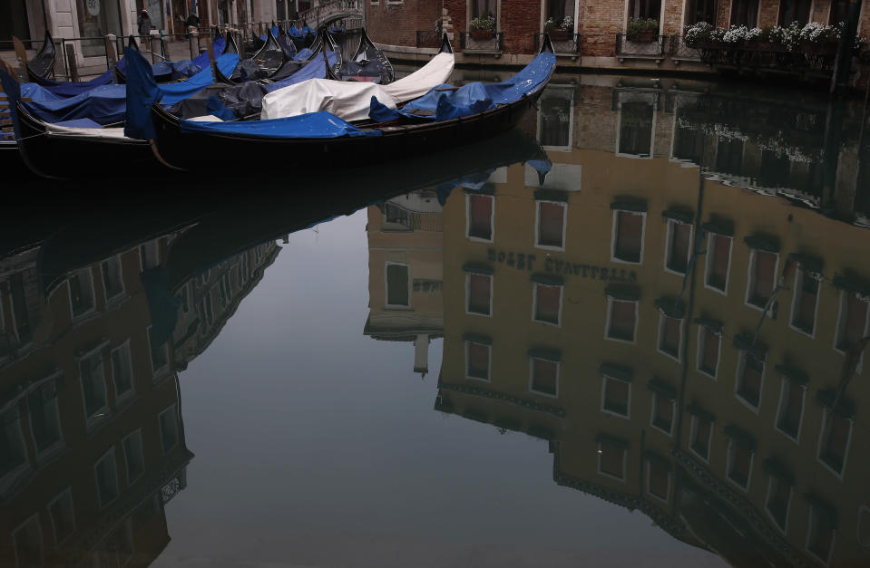 Gondolas are docked in Venice, Italy, Saturday, Jan. 30, 2021. Gondolas and other vessels are moored instead of preparing for Carnival's popular boat parade in the lagoon. Alleys are eerily empty. Venetians and the city's few visitors stroll must be masked in public places, indoors and out, under a nationwide mandate. (AP Photo/Antonio Calanni)