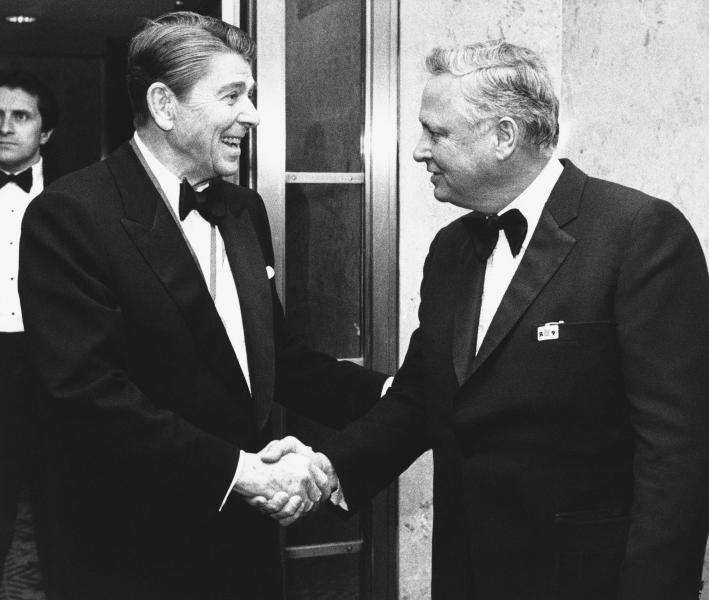FILE - In this Jan. 26, 1985 file photo, President Ronald Reagan, left, shakes hands with Barron Hilton upon his arrival at the Capitol Hill in Washington to attend the annual Alfalfa Club meeting. Hilton, a hotel magnate who expanded his father's chain and became a founding owner in the American Football League, has died. Hilton's family says he died Thursday, Sept. 19, 2019, of natural causes at age 91 in his Long Angeles home. He transformed Hilton into the industry's top brand during his 30 years as its chief executive. (AP Photo/Budd Gray, File)