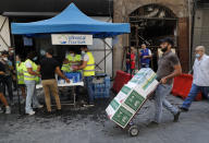 A man carries donated food as he passes in front of a tent that citizens set up to offer people food and drinks, on a street that was damaged by last week's explosion, in Beirut, Lebanon, Tuesday, Aug. 11, 2020. In the absence of the state, acts of kindness and solidarity have been numerous and striking. Many extended a helping hand far beyond their circle of friends or family, taking to social media to spread the word that they have a room to host people free of charge. (AP Photo/Hussein Malla)