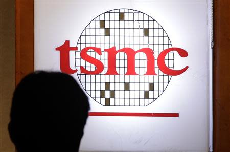 File photo of a man sitting in front of the TSMC logo during an investors' conference in Taipei