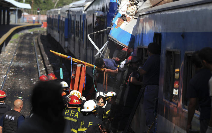 Firemen rescue wounded passengers from a commuter train after a collision in Buenos Aires, Argentina, Wednesday Feb. 22, 2012. A packed train slammed into the end of the line in Buenos Aires' busy Once station Wednesday, killing dozens and injuring hundreds of morning commuters as passenger cars crumpled behind the engine. (AP Photo/Anibal Greco) NO PUBLICAR EN ARGENTINA