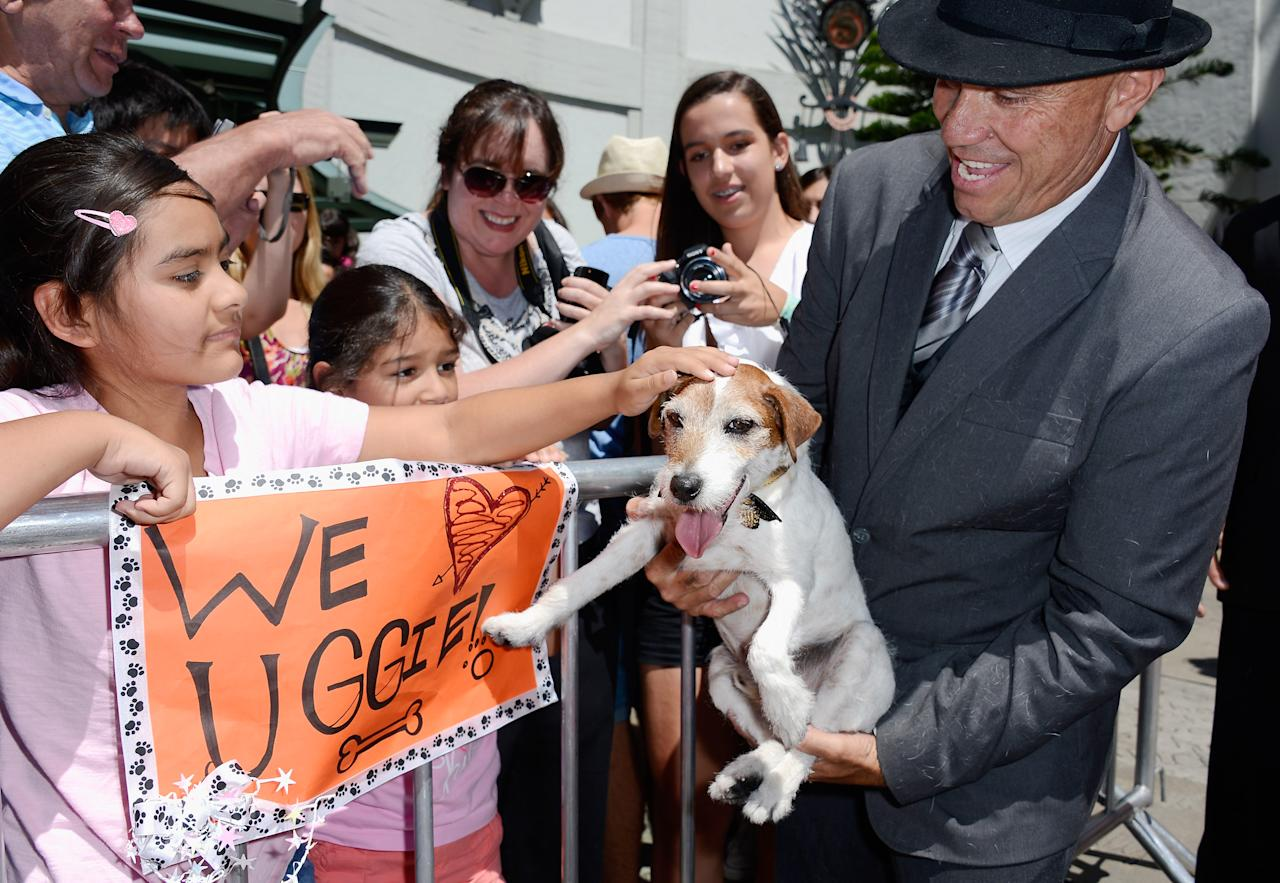 "HOLLYWOOD, CA - JUNE 25: Owner/trainer Omar Von Muller holds up Uggie, the canine star form the film ""The Artist"" which won an Academy Award for Best Picture, as he greets his fans Lucia Tabletos, 9, (L) and her sister Olivai Tabletos, 7, outside Grauman's Chinese Theatre after the movie dog casted his paw prints in cement during a ceremony marking his retirement from show business on June 25, 2012 in Hollywood, California.  (Photo by Kevork Djansezian/Getty Images)"