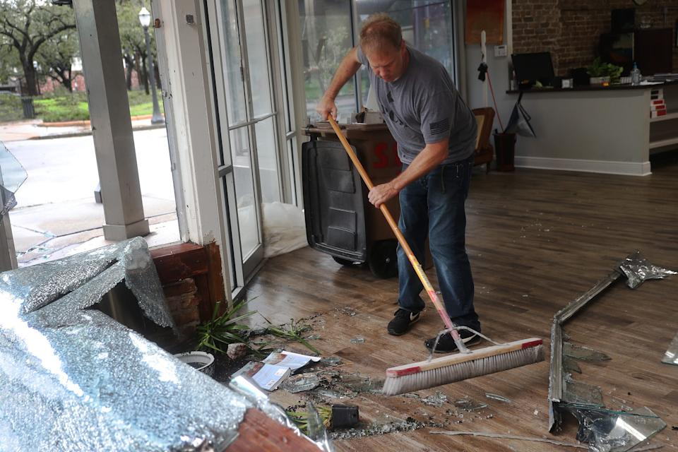 Morgan Griffin cleans up the broken window in the store he works in as Hurricane Sally passes through Mobile, Alabama.