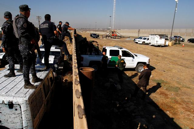 <p>Mexican federal police officers (L) look over the current border fence, while U.S. border patrol authorities visit the site where several prototypes for U.S. President Donald Trump's border wall with Mexico have been built, in this picture taken from the Mexican side of the border, in Tijuana, Mexico, Oct. 26, 2017. (Photo: Jorge Duenes/Reuters) </p>