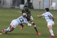 Lukhanyo Am of South Africa is tackled by Santiago Chocobares of Argentina while Jeronimo de la Fuente of Argentina looks on during the second Rugby Championship match between Argentina and South Africa at the Nelson Mandela Bay Stadium, Gqebeha, South Africa, Saturday, Aug. 21, 2021. (AP Photo/Halden Krog)