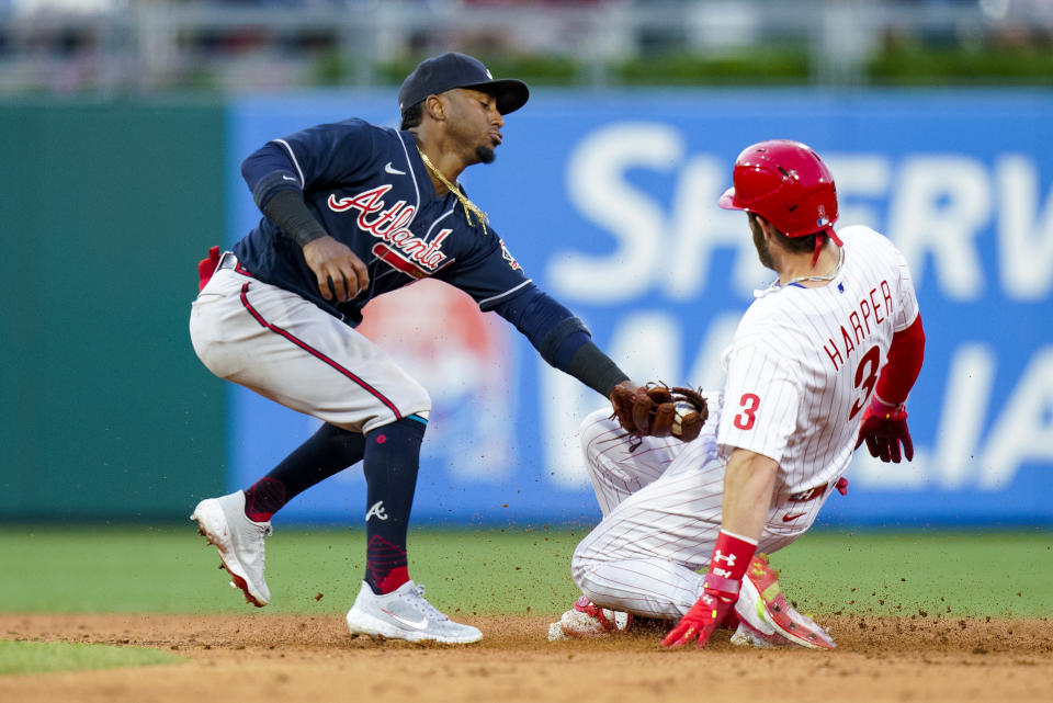 Philadelphia Phillies' Bryce Harper, right, avoids a tag by Atlanta Braves second baseman Ozzie Albies, left, during the third inning of a baseball game, Friday, July 23, 2021, in Philadelphia. (AP Photo/Chris Szagola)