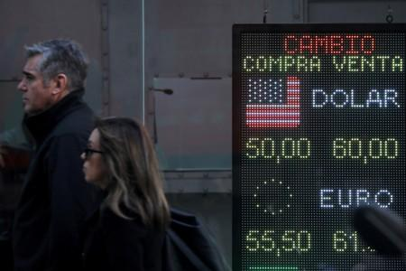 FILE PHOTO: Pedestrians walk past an electronic board showing currency exchange rates in Buenos Aires' financial district