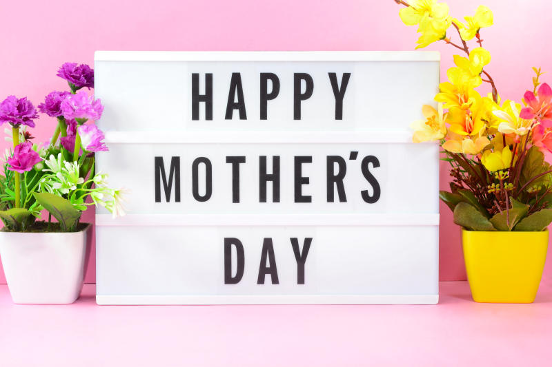 Happy Mothers Day text on light box with flowers on the background.