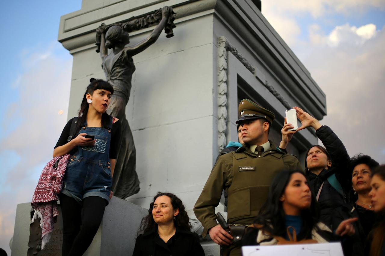 Demonstrators gather next to a police officer during a peaceful march against gender violence in Santiago, Chile, October 19, 2016. REUTERS/Ivan Alvarado