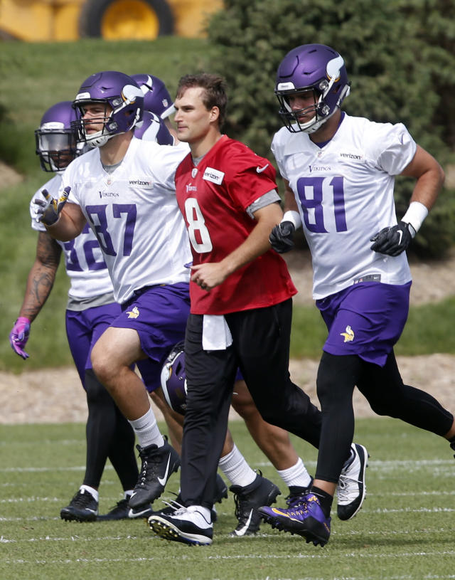 Minnesota Vikings quarterback Kirk Cousins, center, jogs with tight ends Josiah Price, left, and Blake Bell to another field during practice at the NFL football team's training camp in Eagan, Minn., Thursday, June 14, 2018. (AP Photo/Jim Mone)