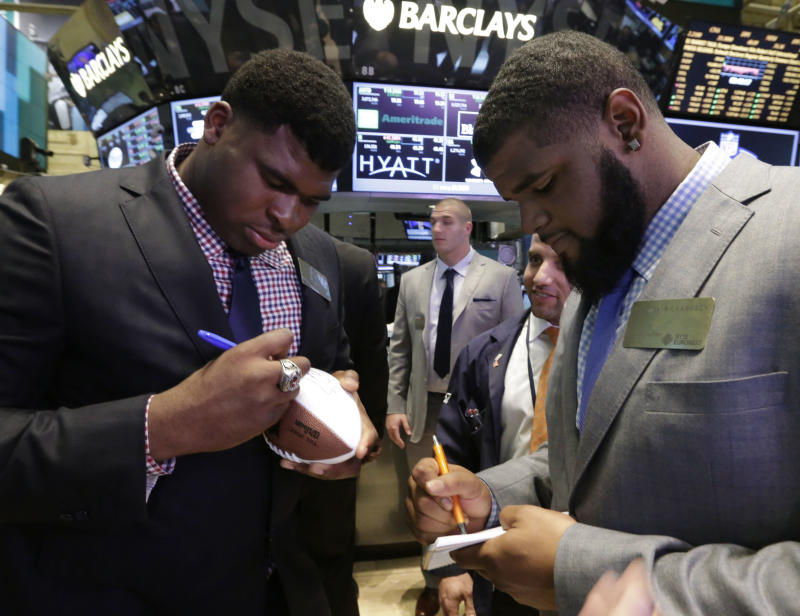 NFL draft prospects DJ Fluker, left, from Alabama, and Sheldon Richardson, of Missouri, sign autographs during their visit to the trading floor of the New York Stock Exchange, Wednesday, April 24, 2013.  (AP Photo/Richard Drew)