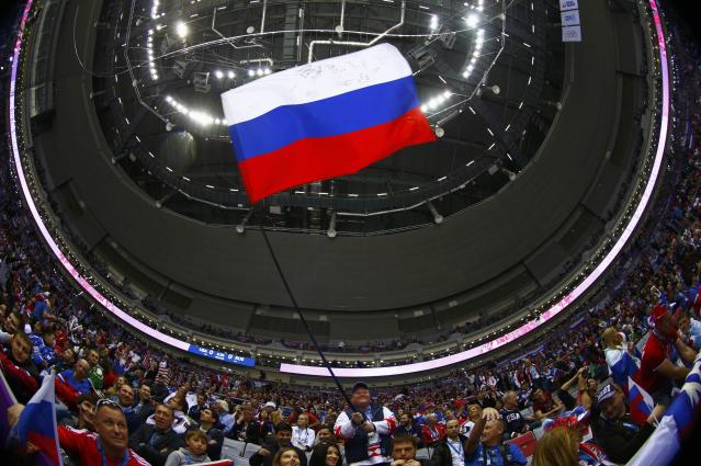 A fan waves a Russian flag before the men's preliminary round hockey game between Russia and USA at the Sochi 2014 Winter Olympic Games February 15, 2014. Picture taken with a fisheye lens. REUTERS/Mark Blinch (RUSSIA - Tags: OLYMPICS SPORT ICE HOCKEY TPX IMAGES OF THE DAY)