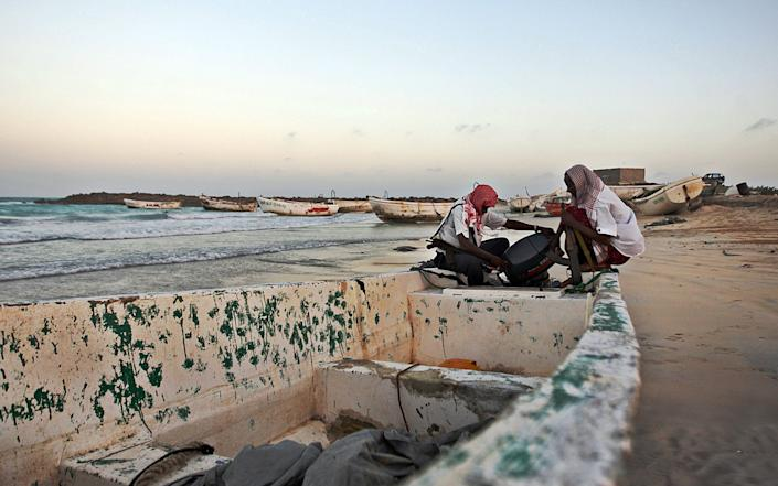 Pirates prepare a boat before going on the hunt from the pirate port of Hobyo, Somalia - AFP