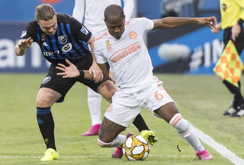 Atlanta United's Darlington Nagbe, right, challenges Montreal Impact's Samuel Piette during first half MLS soccer action in Montreal, Sunday, Sept. 29, 2019. (Graham Hughes/The Canadian Press via AP)