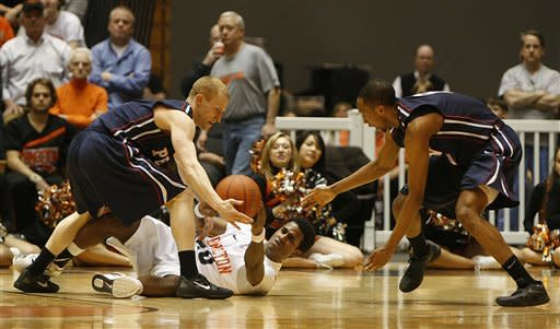 Pennsylvania's Zack Rosen, left, and Miles Cartwright, right, steal the ball away from Princeton's Douglas Davis (20) center, during the first half of an NCAA college basketball game in Princeton, N.J. on Tuesday, March 6, 2012. (AP Photo/Tim Larsen)