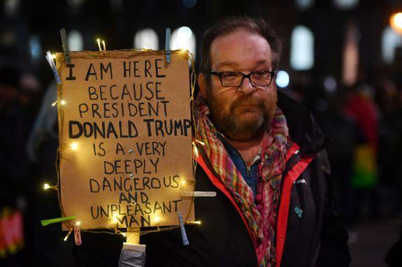 TOPSHOT - Demonstrators protest outside Downing Street against US President Donald Trump in central London on January 30, 2017. President Trump signed an executive order on January 27, 2016 restricting immigration from seven Muslim countries. / AFP / BEN STANSALL (Photo credit should read BEN STANSALL/AFP/Getty Images)