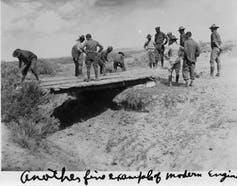 Soldiers assess a plank bridge over a gully.