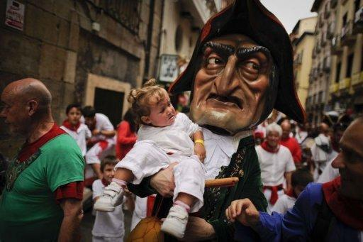 A man dressed as a giant holds a young girl during the giants and big heads parade of the San Fermin festival in Pamplona