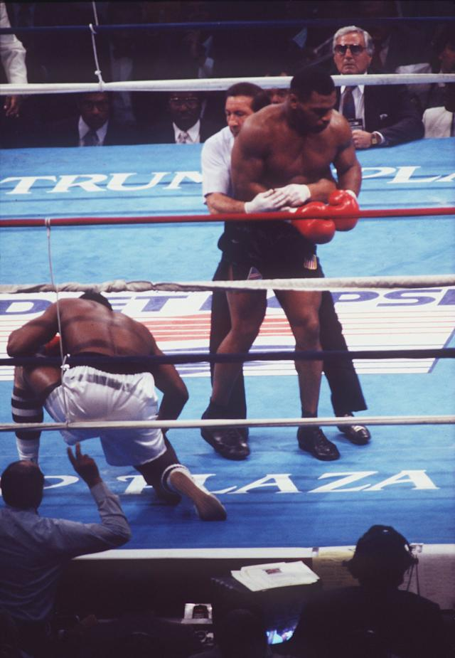 Mike Tyson is restrained after knocking down Michael Spinks in their fight.