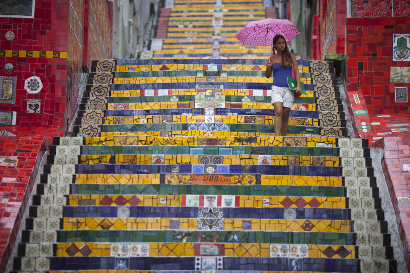 "A woman descends a stairway that was decorated by Chilean artist Jorge Selaron, which he titled the ""Selaron Stairway"" in Rio de Janeiro, Brazil, Thursday, Jan. 10, 2013. Selaron, an eccentric Chilean artist and longtime Rio resident who created a massive, colorful tile stairway in the bohemian Lapa district that's popular with tourists, was found dead on the stairway on Thursday. He was 54. Authorities are investigating the cause of death. (AP Photo/Felipe Dana)"